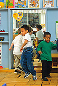 MR / Schenectady, New York. Yates Arts in Education Magnet School. Pre-K class. Boys (4; Including African-American and Caucasian) dance at free play time on stage they created from large blocks. MR: Gar4, McG1, Fen1. © Ellen B. Senisi