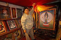 A sealer with a 9 month work Thangka, in one of many shop in Durbari Square in Kathmandu. The lamas who paint thangkas use painting as a form of spiritual education and can spend up to 9 months on each canvas. Thangkas are seen hanging in every temple, monastery and family shrine in Tibet and Nepal..