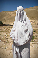 A widow, dressed in a white burqa, in the village of Bachaley.