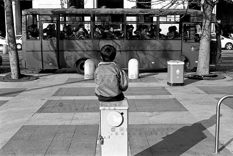 milano, un bambino osserva un autobus di militari sul piazzale della stazione centrale ---- milan,  a kid looks at a military bus on the square in front of central station
