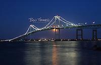 The full moon rises behind Newport Bridge