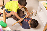 Preschool ages 3-5 two boys struggling over possession of toy mop grabbing and pulling horizontal
