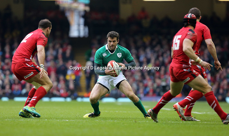 Pictured: Jared Payne of Ireland (C) is trying to avoid Jamie Roberts (L) and Leigh Halfpenny (R) of Wales Saturday 14 March 2015<br /> Re: RBS Six Nations, Wales v Ireland at the Millennium Stadium, Cardiff, south Wales, UK.