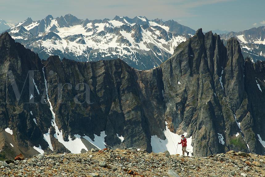 Woman hiking on rocky alpine ridge, Washington's North Cascade Mountains in background, North Cascades National Park, Washington State, USA