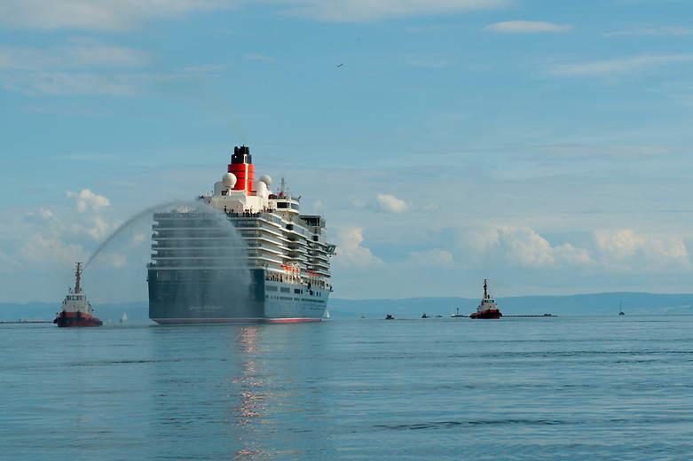 The Queen Elizabeth is being christened by a tugboat as she departs the dockyard on her maiden voyage.  The 294 metre long ocean liner, produced by Fincantieri for Cunard Line, left the Monfalcone dockyards in the Bay of Trieste, Italy on its maiden voyage on the 30th of September 2010. It has 1,046 cabins which can accommodate 2.500 guests and is supported by 1,097 members of staff. Tickets for the inaugural cruise to the Canary Islands were sold out in 29 minutes.