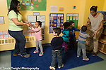 Preschool child care toddler all day program two female teachers dancing with group of children