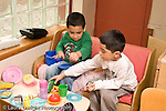 Education preschoool children ages 3-5 pretend play two boys playing together with dishes and toy food in kitchen family area horizontal