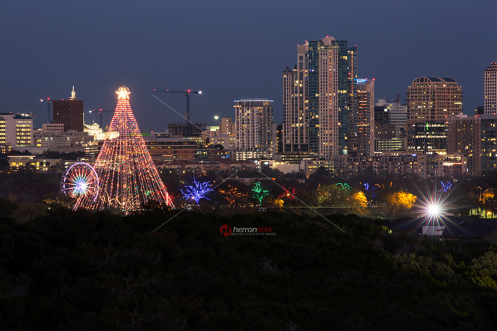 Austin, Texas celebrates the Christmas holiday spirit with the Zilker Holiday Tree, a 155 foot Christmas tree made from a moonlight tower located in Zilker Park. The visible construction cranes are evidence of the ever growing Austin Skyline, a real estate boom and the fastest growing city in America.