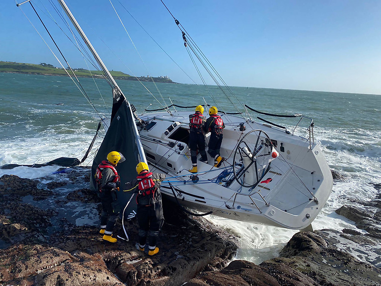 Coastguard volunteers attend the J109 Jelly Baby aground at Weaver's Point