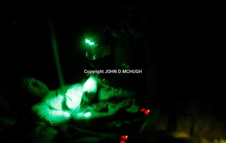 """2 US soldiers, wounded in an Improvised Explosive Deviece (IED) attack, are treated by a medic on a Medevac helicopter from the 101st Aviation Regiment as it flies a rescue mission at night to take them to Forward Operating Base Orgun-E in Paktika province, Afghanistan, 21 July, 2008. Also known by their call sign """"Dust Off"""","""" the Medevac pilots, crew and medics are ready to fly at a moments notice, picking up Coalition soldiers as well as Afghans that require help.(John D McHugh)"""