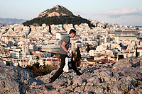 Pictured: A lone tourist climbs onto the rock of Areios Pagos next to the Acropolis.<br /> Re: Police patrol the streets to enforce the measures of self-isolation in an effort to fight the Coronavirus Covid-19 pandemic in Athens, Greece.