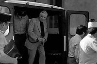 Palais de Justice. 20 juillet 1976. plan 3/4 de 3/4 face de Claude Birague descendant du fourgon cellulaire, est menotté et accompagné d'un policier. Cliché pris le jour où Claude Birague a été présenté et auditionné au Parquet par le juge d'instruction M. Ducasse dans le cadre de l'affaire du meutre de René