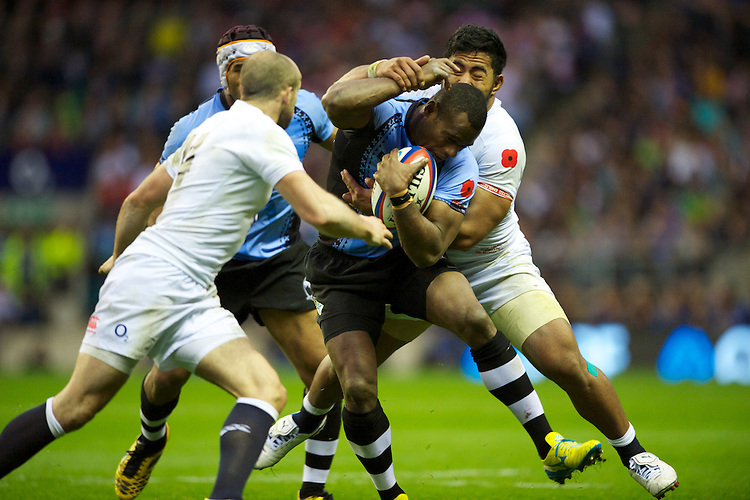 Watisoni Votu of the Flying Fijians is tackled by Manu Tuilagi (right) and Charlie Sharples of England during the QBE International between England and Fiji at Twickenham on Saturday 10th November 2012 (Photo by Rob Munro)