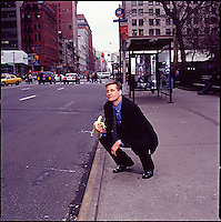 Man in suit kneeling on the sidewalk holding a banana and posturing as an ape