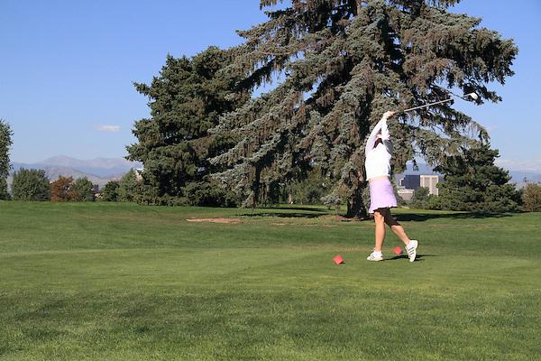 Caucasian  woman driving the golf ball at City Park Golf Course, Denver, Colorado, USA