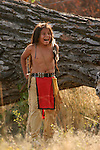 A young Native American Sioux Indian boy laughing outside by a large fallen tree