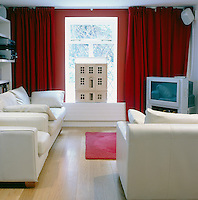 A family room with an entire wall painted red and lined with red curtains. The white leather seating gives a cinema feel to the space.