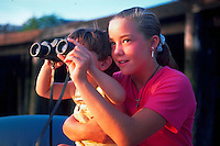 Girl helping younger brother look through a pair of binoculars.