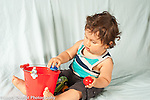 Infant development 12 month old baby boy sitting playing with bucket and toy balls dropping one into bucket