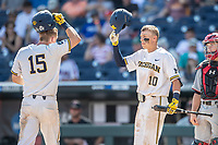 Michigan Wolverines third baseman Blake Nelson (10) greets teammate Jimmy Kerr at the plate during Game 11 of the NCAA College World Series against the Texas Tech Red Raiders on June 21, 2019 at TD Ameritrade Park in Omaha, Nebraska. Michigan defeated Texas Tech 15-3 and is headed to the CWS Finals. (Andrew Woolley/Four Seam Images)