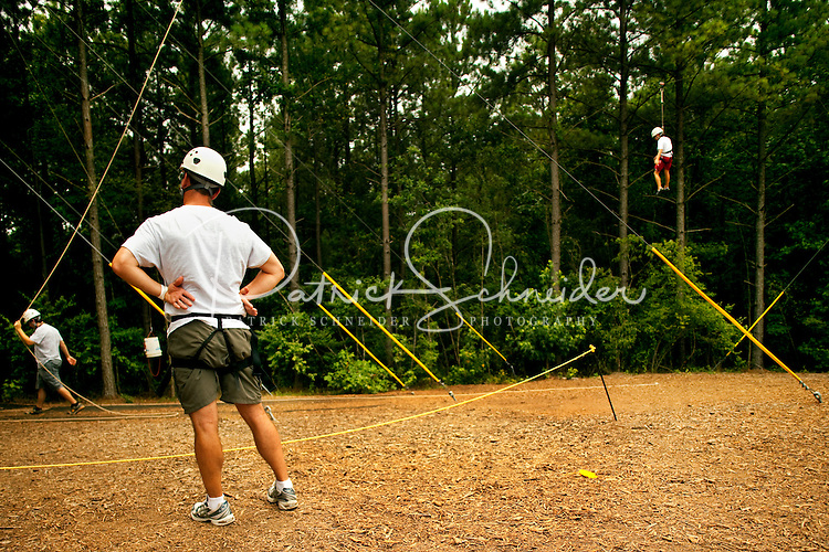 High adventure participants get ready to take flight, zooming through the air over the US National Whitewater Center (USNWC) on the USNWC's zip-lines, part of the facilities high-adventure offerings. The popular outdoor adventure activity lets outdoor enthusiasts be secured into a harness then propelled by gravity along an inclined steel cable. Charlotte, North Carolina's US National Whitewater Center offers multiple zip lines, which vary in height and distance traveled, as well as one of the largest outdoor climbing facilities in the world. The USNWC is a non-profit outdoor recreation facility open to the public for whitewater rafting, kayaking, canoeing, rappelling, zip lining, mountain biking, hiking, climbing and more. The center opened to the public in 2006.