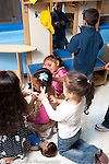 """Education preschool 3-4 year olds group of girls playing beauty parlor hair salon """"cutting"""" hair as boy in dressup looks at self in mirror vertical pretend play"""