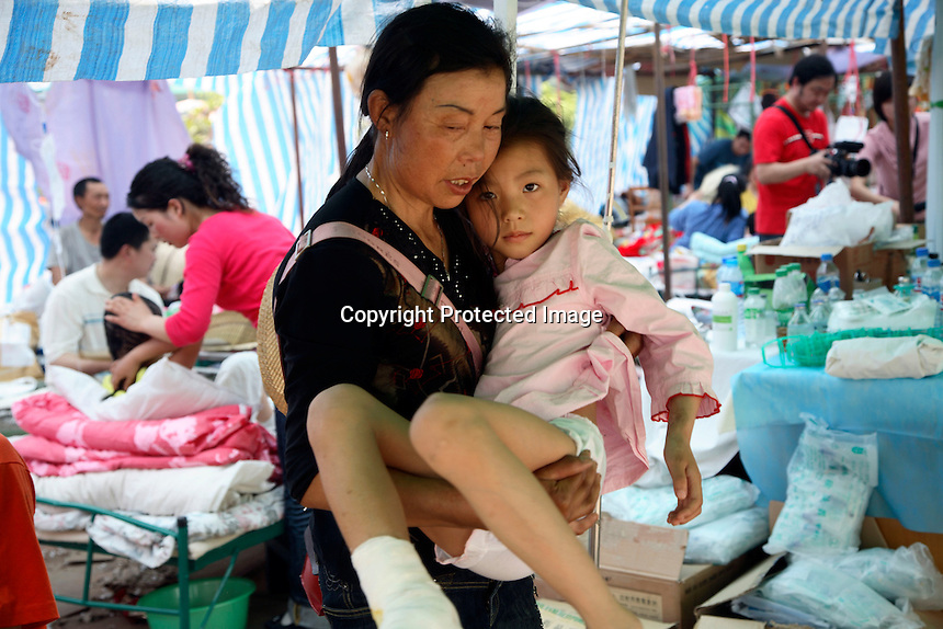 Chen Si, a seven year old first grader who sustained a broken ankle, being lifted by her grandmother at a temporary hospital shelter in Deyang, Sichuan, China..16 May 2008