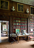16th century portait paintings hang below an ornate plasterwork cornice in the library