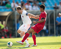 CHARLOTTE, NC - JUNE 23: Scott Arfield #8 holds off Alejandro Portal #8 during a game between Cuba and Canada at Bank of America Stadium on June 23, 2019 in Charlotte, North Carolina.
