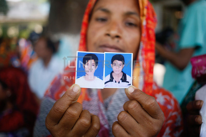 A Bangladeshi woman holds photographs of her two son, victim of the Rana Plaza building on the one-year anniversary of the garment factory building collapse in Savar, near Dhaka, Bangladesh.