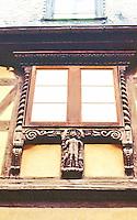 Riquewihr: Carved fenestration on building.