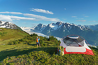 Hiker takes a picture by a tent camp overlooking the Spencer glacier in the Chugach National Forest, Kenai Peninsula, Alaska.