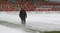 A member of the Brentford ground staff clears the snow away from the lines ahead of kick-off  during Brentford vs Leicester City, Emirates FA Cup Football at the Brentford Community Stadium on 24th January 2021