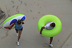 Couple walking with inner tubes in Confluence Park, Denver, Colorado, USA.