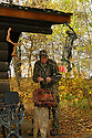 00105-042.03 Bowhunting (DIGITAL) Archer ckecks map while at hunting shack.  Deer stand, backpack, rattling antlers, Realtree Camo.  V5F1