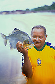 Tataquara, Brazil. Antonio, a local guide, wearing a Brazil football shirt holding a pacu fish.