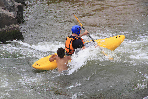 Kayaker rescuing a swimmer in whitewater, Denver, Colorado, USA.
