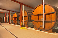 A storage room in the winery with old wooden foudre (large wooden barrels) Chateau Thieuley La Sauve Majeure Entre-deux-Mers Bordeaux Gironde Aquitaine France