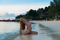 Girl practicing yoga in pigeon pose on the beach with Thai longtail boats, Ko Lipe, Thailand