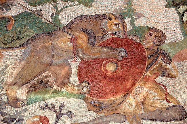 A Lion attacking a hunter with a shield in a  Lion Hunt. Roman mosaics at the Villa Romana del Casale which containis the richest, largest and most complex collection of Roman mosaics in the world. Constructed  in the first quarter of the 4th century AD. Sicily, Italy. A UNESCO World Heritage Site.