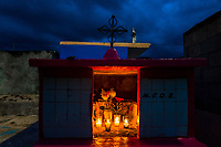 """Burning candles, flowers and wooden crates are seen placed inside a niche during the bone cleansing ritual at the cemetery in Pomuch, Mexico, 28 October 2019. Every year on the Day of the Dead, people of Pomuch, a small Mayan community in the south of Mexico, visit the cemetery to take part in a pre-Hispanic tradition of cleaning of bones of their departed relatives (""""Limpia de huesos""""). People who die in Pomuch are firstly buried for three years in an above-ground tomb then the dried-up bodies are taken out, bones are separated, wrapped in a decorated cloth, put into a wooden crate, and placed on display among flowers for veneration."""