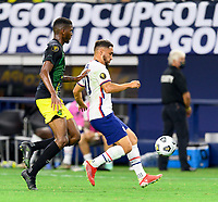DALLAS, TX - JULY 25: Cristian Roldan #10 of the United States attempts to gain control of a loose ball in front of Damion Lowe #17 of Jamaica during a game between Jamaica and USMNT at AT&T Stadium on July 25, 2021 in Dallas, Texas.