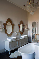 An antique sideboard has been adapted into a washstand for a pair of basins in this elegant bathroom