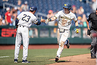 Michigan Wolverines first baseman Jimmy Kerr (15) is congratulated by third base coach Nick Schnabel (23) after his second home run in Game 11 of the NCAA College World Series against the Texas Tech Red Raiders on June 21, 2019 at TD Ameritrade Park in Omaha, Nebraska. Michigan defeated Texas Tech 15-3 and is headed to the CWS Finals. (Andrew Woolley/Four Seam Images)