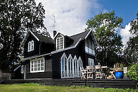 The gabled cottage is surrounded by a terrace painted in traditional black and white