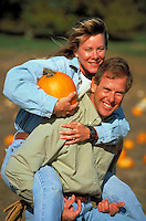 Man and woman have fun as they pick pumpkins on a nice autumn day.