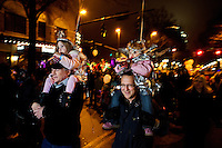 Families of parents, grandparents and children watch a downtown parade during First Night Charlotte 2010. The family-friendly public event (no alcohol allowed) is an annual cultural New Year's Eve celebration held in downtown / uptown / Charlotte center city. Charlotte First Night - An Imagination Celebration brought together artists, musicians, dancers and more from across the country. The New Year's event is organized by Charlotte Center City Partners, which facilitates and promotes the economic and cultural development of this North Carolina urban core.