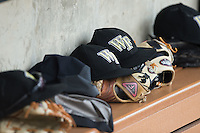 Wake Forest Demon Deacons caps sit on top of Louisville Slugger gloves in the home dugout during the game against the Clemson Tigers at David F. Couch Ballpark on March 12, 2016 in Winston-Salem, North Carolina.  The Tigers defeated the Demon Deacons 6-5.  (Brian Westerholt/Four Seam Images)