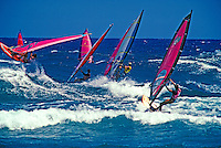 Windsurfers crowd the waves at world famous Hookipa beach on the island of Maui.