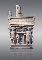 """End panel of a Roman relief sculpted sarcophagus with kline couch lid with a reclining male figuer depicted, """"Columned Sarcophagi of Asia Minor"""" style typical of Sidamara, 3rd Century AD, Konya Archaeological Museum, Turkey. Against a grey background"""